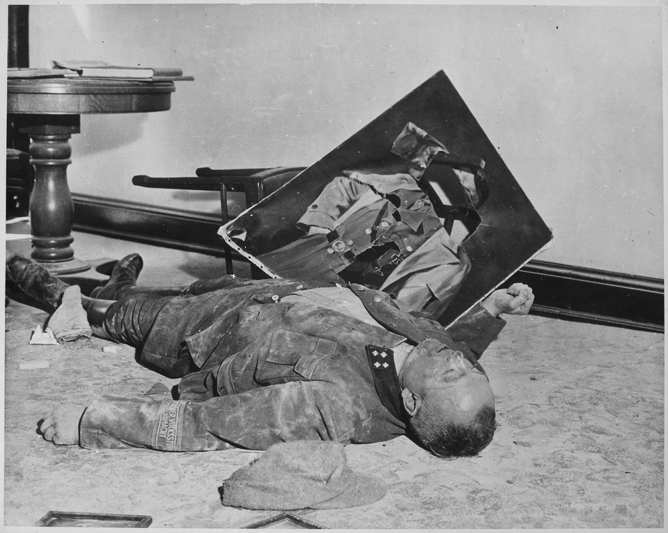With torn picture of his feuhrer beside his clenched fist, a dead general of the Volkssturm lies on the floor of city... - NARA - 535982