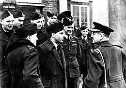 Half-length outdoor portrait of moustacioed man in military great coat with peaked cap, talking to a group of ten or men in military uniforms with forage caps