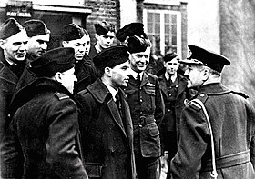 Half-length outdoor portrait of moustachioed man in military great coat with peaked cap, talking to a group of ten or men in military uniforms with forage caps