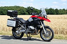 Black, silver and red BMW R1200GS parked on a road by the side of a field of mature wheat