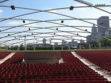 A large number of red seats with a green lawn and park behind, beneath a symmetic curving metal trellis with speakers. Skyscrapers are in the distant background.