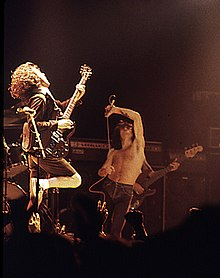 Former vocalist Bon Scott (centre) pictured with guitarist Angus Young (left) and bassist Cliff Williams (back), performing at the Ulster Hall, August 1979.