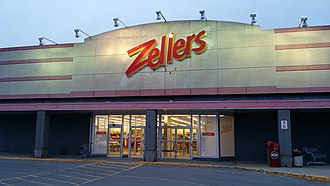 """Zellers - The store front of the re-opened Zellers in Bells Corners, part of Nepean in Ottawa. The new Zellers sign in the foreground with the shadows of the previous Zellers sign, including the """"Truly Canadian"""" and the maple leaf, behind it."""