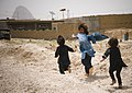 Afghan children play near U.S. military on patrol (4665782053).jpg