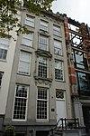 foto van Pand met zandstenen gevel onder rechte triglyfenlijst en attiek, met gebeeldhouwde vensteromlijsting in de as, gebeeldhouwde stoep en deur en kelderpui