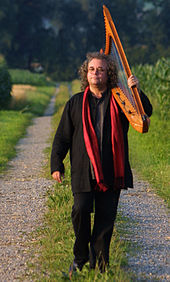 A man wearing black clothing and a red scarf, walking along a gravel path and carrying a harp over his shoulder