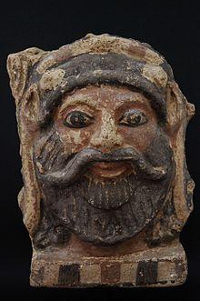 Antéfix (motif initialement placé sur un toit ou une corniche) en terre-cuite peint en noir et en rouge représentant la tête d'un homme souriant avec une barbe et une moustache.