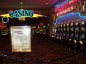 "A roped off entrance to room with a neon sign ""CASINO"", over a sign saying ""CASINO A... CLOSED"". The room contains many slot machines. Nobody is in the room."