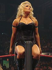 A blond woman sits on the turnbuckle of a wrestling ring, facing away from the ring while having a leg on either side of the ring post. She is wearing a black halterneck corset with a short black skirt and black wrestling boots.