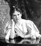 Photo of Blanche Blick Burnham taken in 1896 in Bulawayo, Rhodesia. She is seated at a table and her head is leaning on her right arm. She is wearing a flowing dress.
