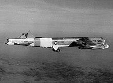 Fotografía en blanco y negro de un B-52 en vuelo con su estabilizador vertical cortado.