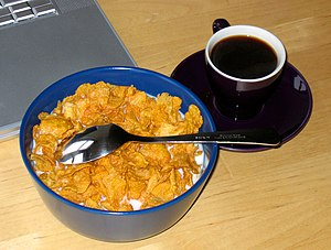 Breakfast cereal - A bowl of corn flakes with milk.
