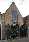 foto van Stalgebouw met gepleisterde puntgevel. Getoogde poort en zoldervensters. Stoeppaal