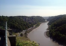River flowing though a steep sided valley. In the distance is a suspension bridge supported by towers. In the left foreground is a handrail.