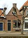 foto van Huis met gepleisterd puntgeveltje met uitgekraagde toppilaster
