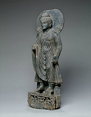 Ṛddhi - Statue of Buddha performing the Miracle at Śrāvastī, with flames above his shoulders. Gandhara, 100-200 CE