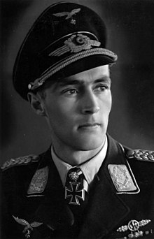 The head and shoulders of a young man, shown in semi-profile. He wears a peaked cap and a military uniform with an Iron Cross displayed at the front of his shirt collar.