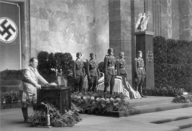 A black-and-white photo of six soldiers standing around a flag-covered coffin. All six soldiers wear steel helmets and numerous military decorations. To the left of the coffin is a lectern with a man in a military uniform speaking into two microphones on the lectern. The wall behind the coffin and lectern is draped with a swastika flag. To the right of the lectern is a pillar with an iron cross on the front and an eagle sitting on top.