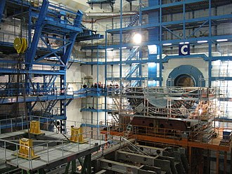 ATLAS experiment - ATLAS experiment under construction in October 2004 in the experiment pit. Construction was completed in 2008 and the experiment has been successfully collecting data since November 2009, when colliding beam operation at the LHC started. Note the people in the background, for size comparison.