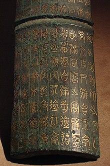 Photographie d'un objet en cuivre, de la forme d'une tuile, sur lequel sont gravés des caractères chinois anciens.