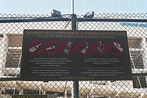 שלט מחוץ לאצטדיון קאמפ נואו, המראה אילו חפצים מסוכנים אינם מורשים להיכנס לתחומי האצטדיון.