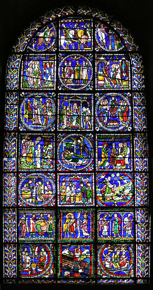 "The window has a simple round-arched top. The stained glass is supported by a lead armature of squares and circles which divide it into many separate pictures. The upper pictures show the story of the Three Wise Men. The lower part has an assortment of Biblical scenes including ""The Sower"". The background colour is deep blue."