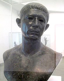 "A bronze bust of the head and shoulders of a middle-aged man, with the word ""CATO"" inscribed across the chest"