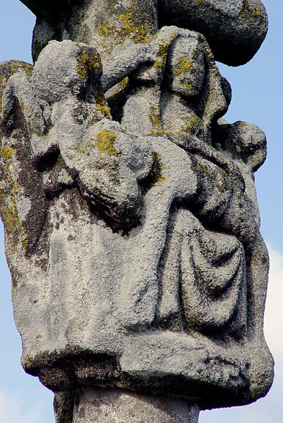 "Angels lovingly lift the edges of the Virgin Mary's veil from her face in the pietà on the Calvary known as the ""Calvaire du Beron"""