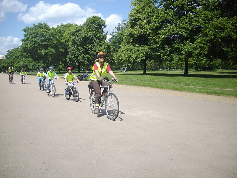 File:Children and their coach cycling in Hyde Park in London..jpg