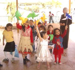 "Aqabah - Children of kindergarten slated for demolition holding ""pinwheels for peace."""