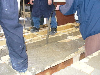 Vibrator (mechanical) - A handheld concrete vibrator consolidates fresh concrete in a wooden form for a concrete beam.