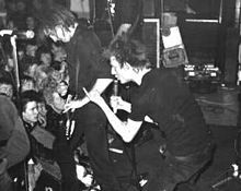 Two members of the rock band Crass are shown at a performance. From left to right are an electric guitarist and a singer. Both are dressed in all black clothing. The singer is making a hand gesture.