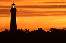 The Sunset Behind Lighthouse Looking Up From Beach