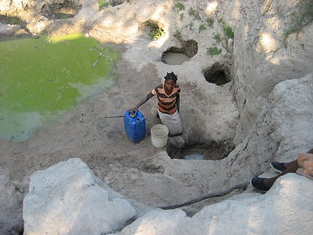 Woman fetching water during the dry season from a polluted source in Machaze District of the Central Manica Province. Daily struggle for water (5400691444).jpg