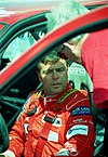 Derek Warwick in a racing suit sitting in a touring car being spoken to a team member
