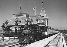 A black-and-white image of a train parked in front of a railroad station with the logo of the Atchison, Topeka and Santa Fe Railway visible on its roof