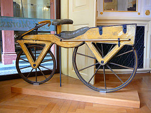 "Karl Drais - A Draisine, also called Laufmaschine (""running machine""), from around 1820. The Laufmaschine was invented by the German Baron, Karl von Drais, at Mannheim in 1817. Being the first means of transport to make use of the two-wheeler principle, the Laufmaschine is regarded as the archetype of the bicycle. The above Draisine was built with cherry tree wood and softwood. One is displayed at the Kurpfälzisches Museum in Heidelberg, Germany."