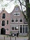 foto van Huis waarvan de gevel wordt beëindigd door een klokvormige top onder rollagen