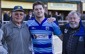 Parramatta Two Blues - Two Blues captain Andrew Cox, achieving 100 first grade games in 2011, is congratulated by President Geoff Baldwin and the oldest living former Wallaby Eric Tweedale