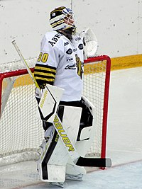 An ice hockey player standing in the goals with his body turned to the right of the camera. He is wearing a black and white uniform.