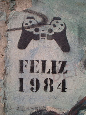 "Stencil graffiti - ""Happy 1984"" - Stencil graffiti found on the Berlin Wall in 2005. The object depicted is a DualShock video game controller."
