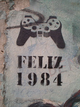 "Nineteen Eighty-Four - ""Happy 1984"" (in Spanish or Portuguese) stencil graffito, denoting mind control via a PlayStation controller, on a standing piece of the Berlin Wall, 2005."
