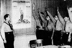 photographie en noir et blanc. Posant devant une affiche expliquant le programme du Francisme, des militants en uniforme font le salut nazi