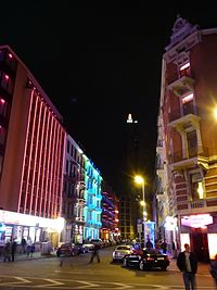 A city street at night, with many colourfully lit buildings. On the left is a large, red tower.