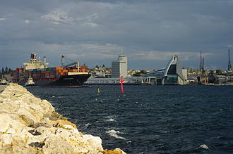 Fremantle Harbour - A container ship leaving the port. The tall building at the centre are the port's administration offices and the Western Australian Maritime Museum is to the right.