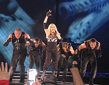 Left profile of a blond female in a tight black dress with gloves and wrist bands singing. A number of similarly dressed dancers encircle her while the backdrop depict black and blue imagery. Several hands holding mobile phones can also be seen.