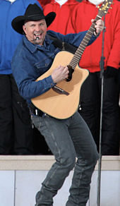 A man in a black cowboy hat, blue shirt and jeans, playing a guitar and singing into a microphone