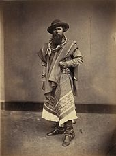 Full-length photograph of a bearded man wearing a wide-brimmed hat, bandana, serape, leather boots and grasping the handle of a long knife in his left hand