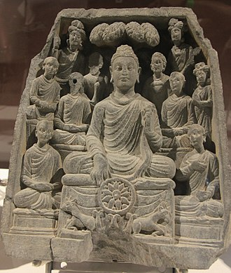 Refuge (Buddhism) - Gautama Buddha delivering his first sermon in the deer park at Sarnath, Varanasi with his right hand turning the Dharmachakra, resting on the Triratna symbol flanked on either side by a deer. Statue on display at the Chhatrapati Shivaji Maharaj Vastu Sangrahalaya in Mumbai.