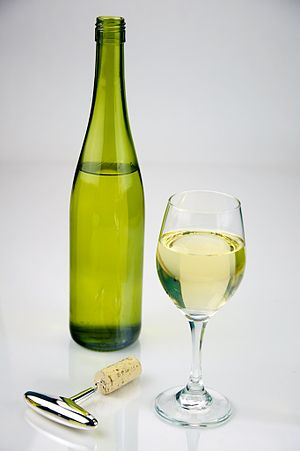 English: Glass of White Wine shot with a bottl...